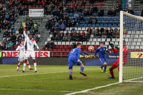 Domácí hráč hlavičkuje na branku Olympiqu a obránce Lyonu signalizuje ofsajd
